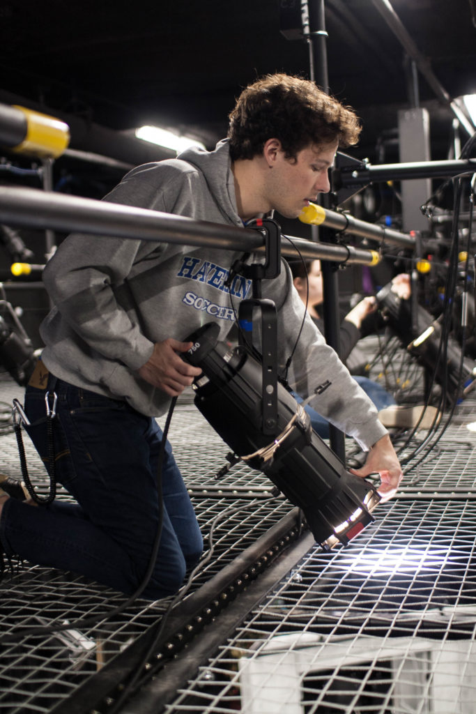 Student focusing lights on SkyDeck tension wire grid at Liberty University.