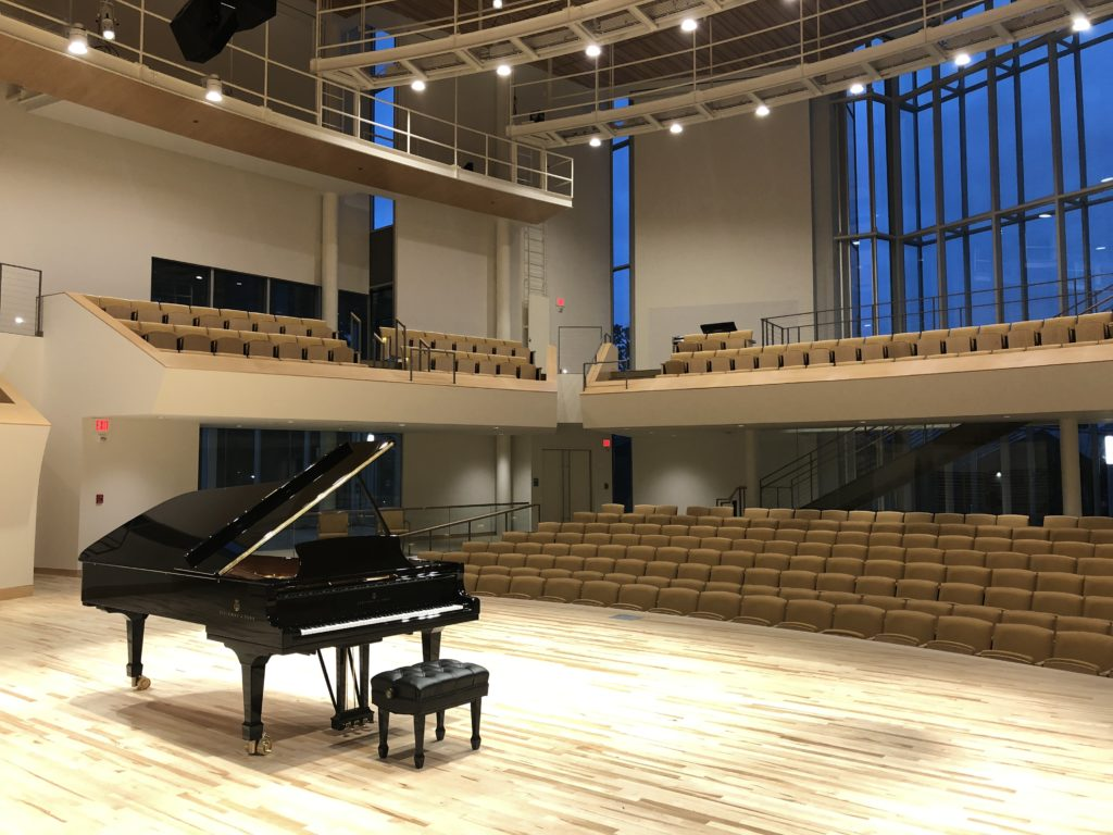 Grand piano center stage at Penn State's Esber Recital Hall with curved SkyDeck tension wire grid visible in upper right-hand corner.